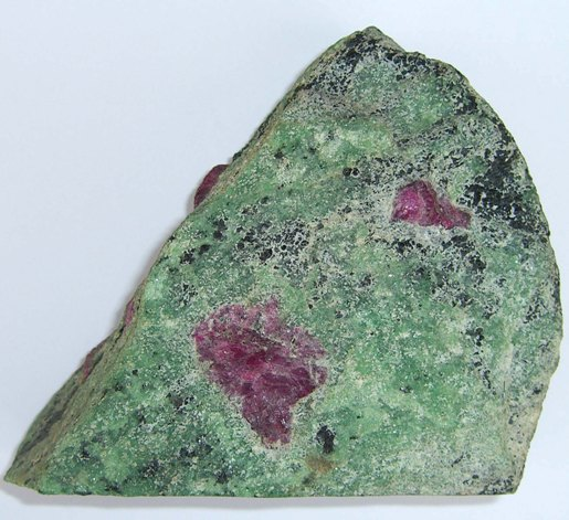 Anyolite from the Merkerstein area of Northern Tanganyika. Apple green zoisite, red ruby corundum and very dark green hornblende. The cut side of the specimen is 11cm long.
